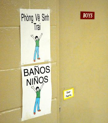 At J.S. Aucoin Elementary School in Amelia, the student population is so ethnically diverse that signs like these, indicating the boys' bathroom, are often necessary in three languages. While 70 percent of the school's students are either Hispanic or Vietnamese, 40 percent of those are identified as not yet being proficient in the English language.