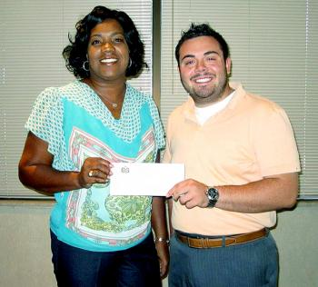 The City of Patterson received a donation from Patterson State Bank to be used in purchasing necessary items to host a Business After Hours event at City Hall held Oct. 17. Sandra Turner, left, head customer service representative for Patterson State Bank, provides Ryan Aucoin of the City of Patterson with a check for the donation.