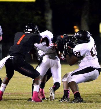 Patterson's Kendall Hunter, left, and Earl Johnson converge on a Donaldsonville ballcarrier during the squads' district  contest Friday. Patterson's defense limited the Tigers to just 125 yards of total offense in the Lumberjacks' 50-7 drubbing.